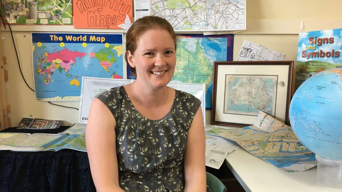 ITAC teacher assistant graduate sitting infront front of school geography activities.