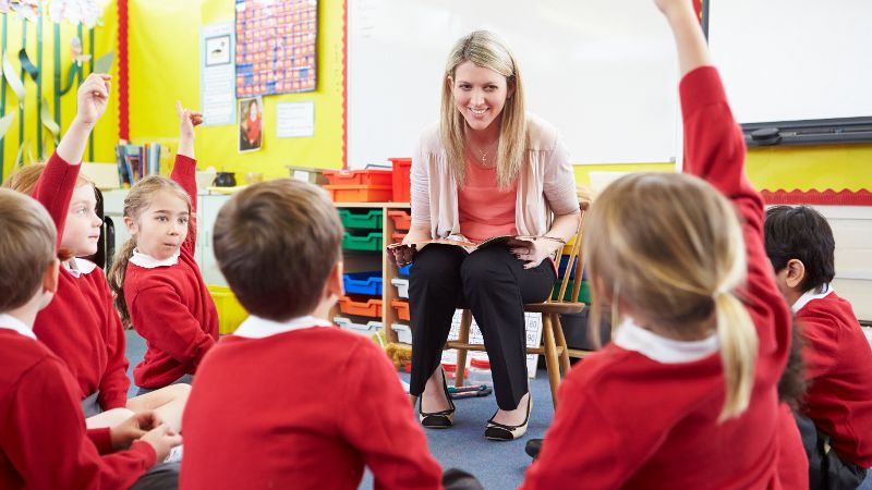 Teacher assistant engaging with a group of students in a classroom environment.