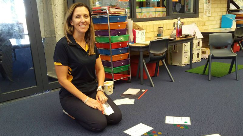 Teacher assistant in classroom with numeracy activities.