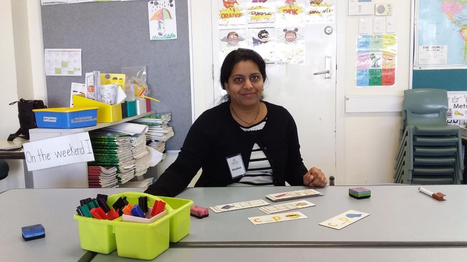 Female teacher aide sitting at desk with picture cards ready for student learning.