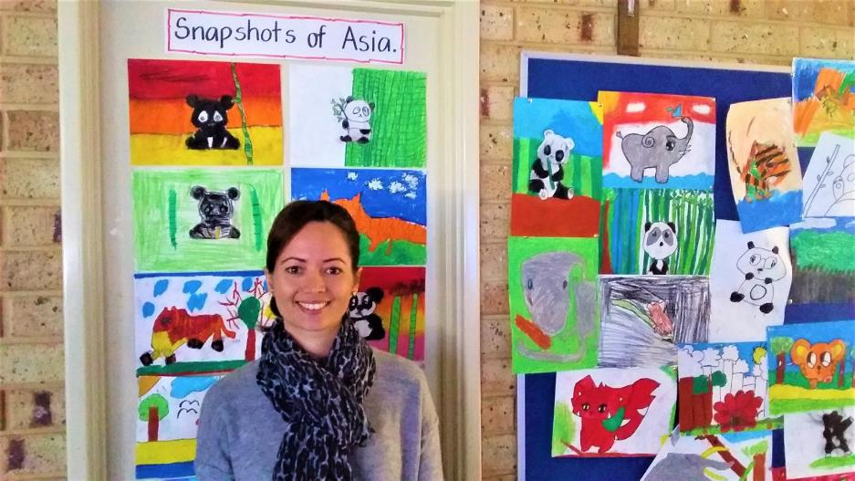 Happy female teacher aide standing in front of colourful drawings of animals made by children.