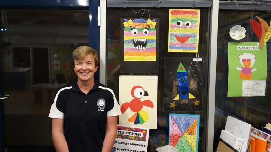 Teacher aide shows us the artwork completed by her students.