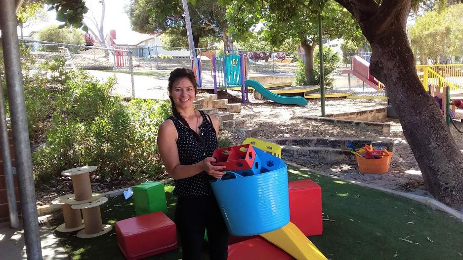 Caucasian teacher aide in playground sorting and packing toys.