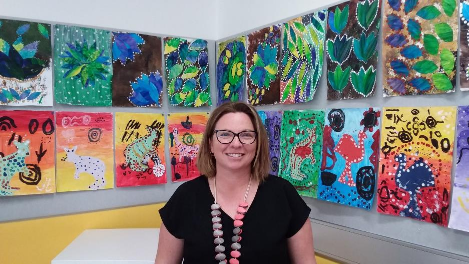 Caucasian female teacher aide with big smile, standing in front of artwork of animals and flora created by children in her class.