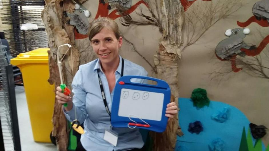 Female teacher aide holds up drawing board in front of art display of trees and Koalas.