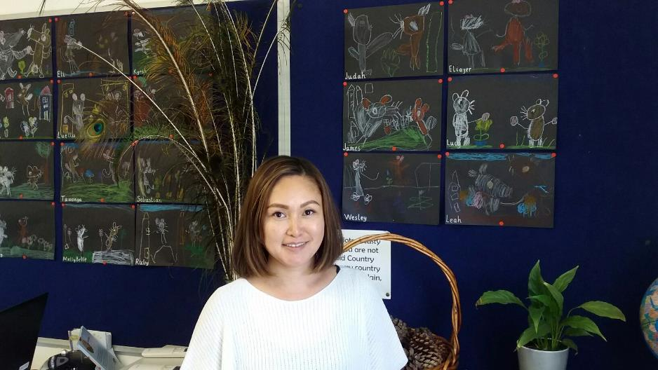 Asian female teacher aide in front of peacock feathers and hanging artwork.