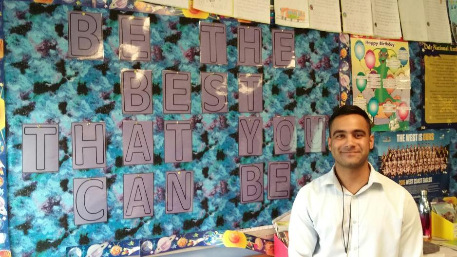 Male teacher aide standing in front of mural that says, 'be the best that you can be'.