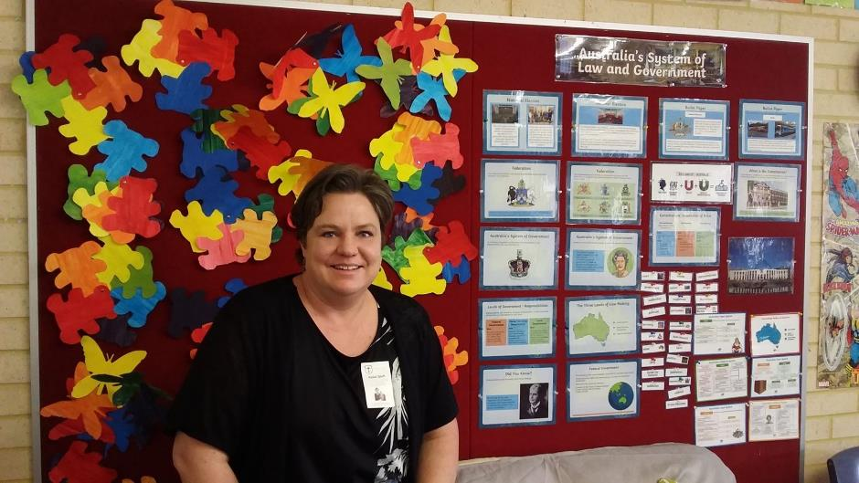 Teacher aide in front of pin-board covered in images and information about the Australian legal system.