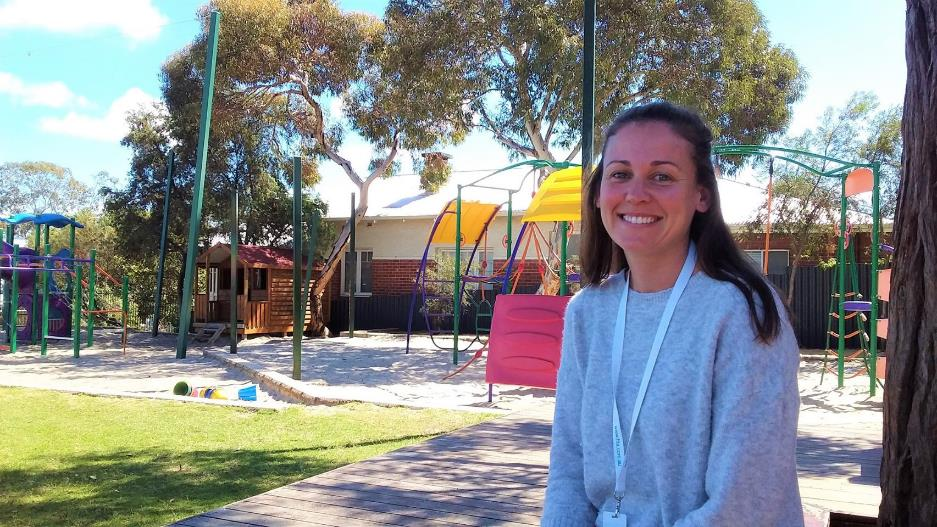 Young smiling female in grey jumper standing in front of colourful playground.