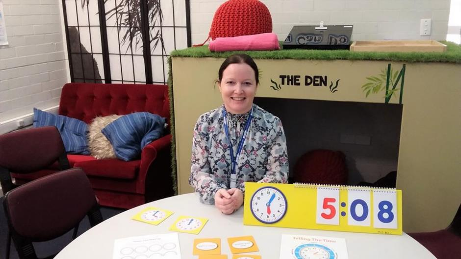 Female teacher aide at desk with resources to teach time.