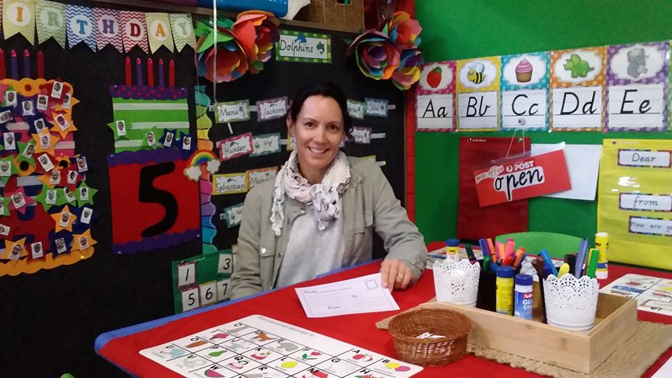 Teacher aide in grey jacket sitting at red desk and surrounded by colourful posters with letters and numbers.