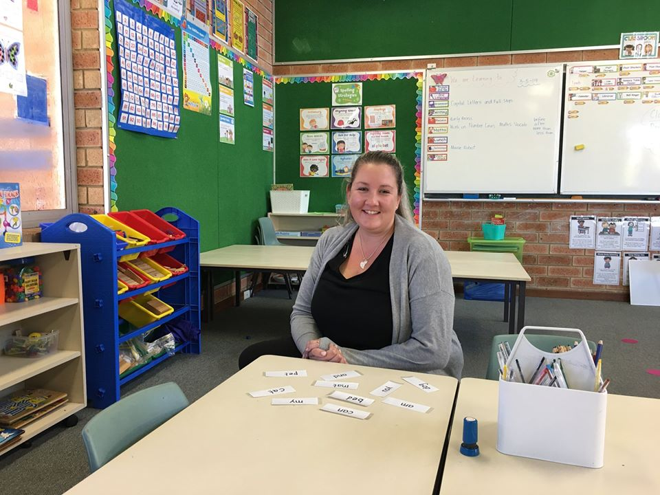 Female teacher aide at desk ready for student activity with flip cards.