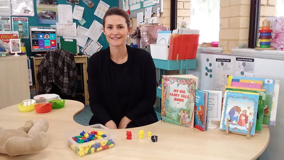 Female teacher aide sitting in child's desk in front of reading books.