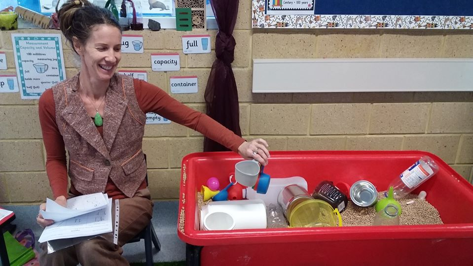 Female teacher aide showcasing equipment used for science experiments and to teach measurement (volume of containers).
