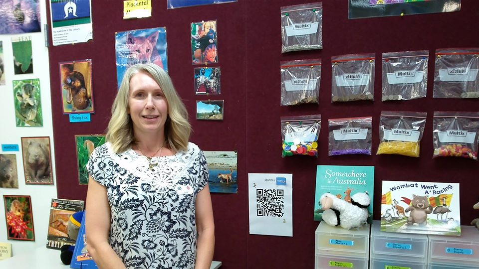 Teacher aide standing in front of pin board with array of animal pictures.
